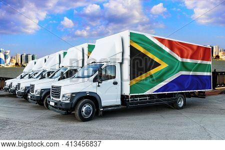 South Africa Flag On The Back Of Five New White Trucks Against The Backdrop Of The River And The Cit