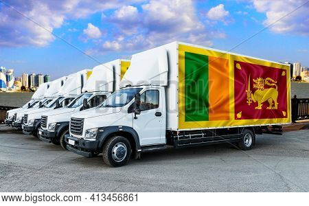 Sri Lanka Flag On The Back Of Five New White Trucks Against The Backdrop Of The River And The City.