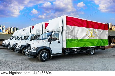 Tajikistan Flag On The Back Of Five New White Trucks Against The Backdrop Of The River And The City.