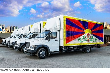 Tibet Flag On The Back Of Five New White Trucks Against The Backdrop Of The River And The City. Truc