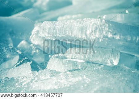 Transparent Shining Clear Ice Icicles Close-up Sparkling On Frozen Wild Lake Shore In Sunset Light.