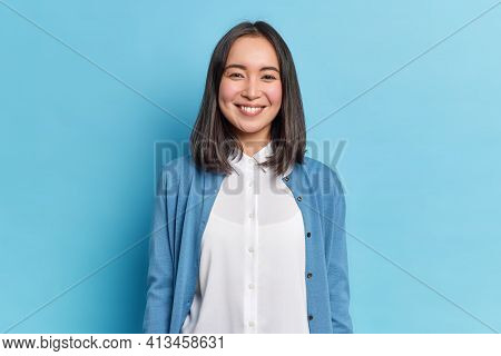 Horizontal Shot Of Pretty Asian Woman With Dark Hair Smiles Pleasantly Looks Directly At Camera Has