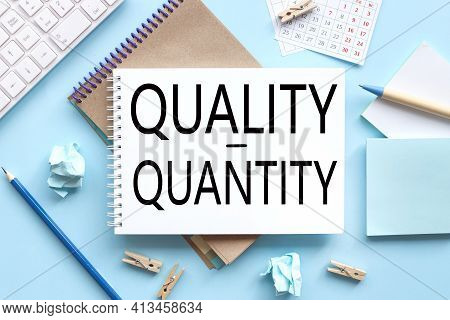 Quality And Quantity. Text On White Notepad Paper On Blue Background. Near The Blue Sticks And A Whi
