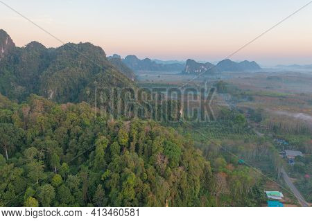 Aerial Top View Of Forest Trees With Fog Mist And Green Mountain Hill At Sunset. Nature Landscape Ba