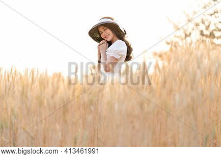 Happy Young Beautiful Woman Wearing Black Hat And White Dress Enjoying Herself Daydreaming In The Go