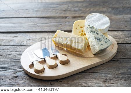 Cheese Board With Camembert Cheese, Parmesan Cheese, Maasdam Cheese. Rustic Food Background.