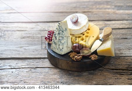 Rustic Wooden Cheese Board With Camembert Cheese, Parmesan Cheese, Maasdam Cheese.