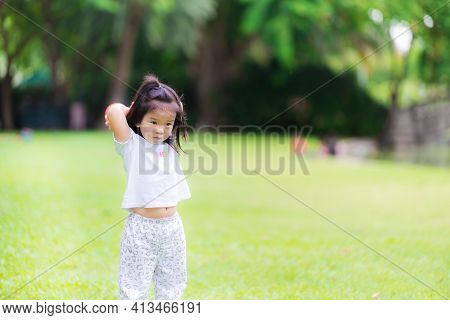 Asian Girl Pretends To Throw An Orange Ball In Her Hand Behind Her Head. Children Play On The Bright