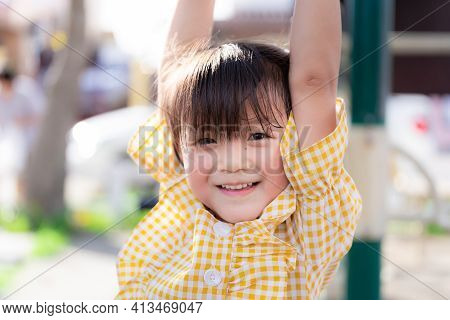 Closeup, Asian Adorable Girls Trapeze For Exercise. Cute Kids Wearing A Yellow Blouse. Child Smiles