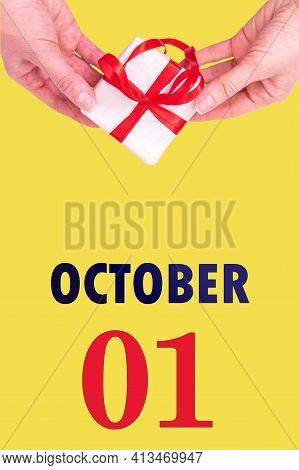 October 1st. Festive Vertical Calendar With Hands Holding White Gift Box With Red Ribbon And Calenda