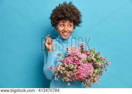 Indoor Shot Of Good Looking African American Woman Holds Bouquet Of Flowers Looks Aside Gladfully Ha