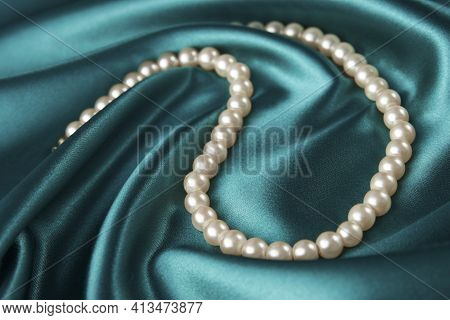 Pearl Necklace On Green Background, Close-up. Luxury Female Jewelry,