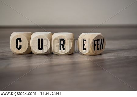Cubes, Dice Or Blocks With Cure And Curfew On Wooden Background
