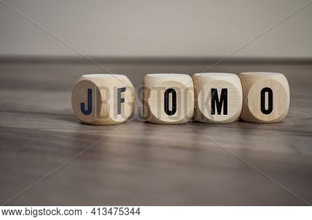 Cubes, Dice Or Blocks With Fomo Fear Of Missing Out And Jomo Joy Of Missing Out  On Wooden Backgroun