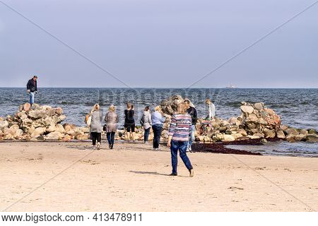 Tourists Take Pictures Of The Lightest Stone Boulders Of The Breakwater On The Coast Of The Gulf Of