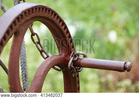 Rusty Well Crank, Locked To A Chain. Blurred Green Background.