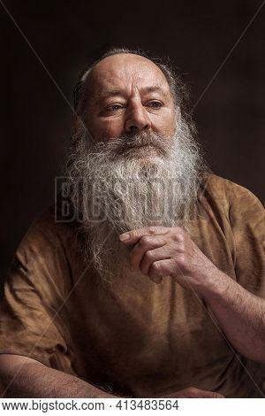 Old Wise Man Holding On To A Long Cigarette
