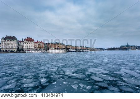 City Pier (stockholm) In Winter. Surface Is Partially Frozen With Shattered Pieces Of Ice. Boats Are