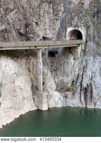 Mountain Tunnel Entrance With A Viaduct Crossing The Lake At High Altitude.