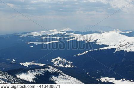View From Above The Mountain Ridges. The Ridges Covered By The Snow, And The Cloudy Sky, Makes The P