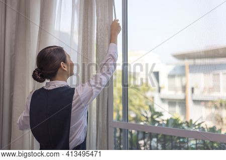 Young Maid Opening Curtains In Hotel Room, Female Housekeeping Chambermaid Opening Window.