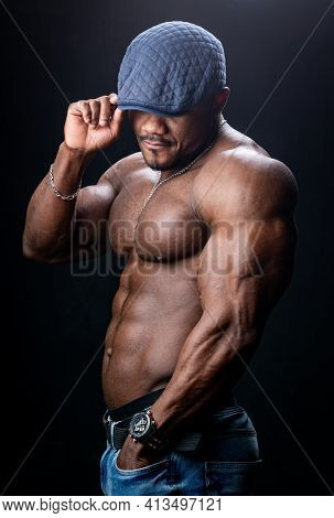 Shirtless Muscular Unrecognizible Man In Cap. Bodybuilder Half Turned To The Camera Poses. Black Stu