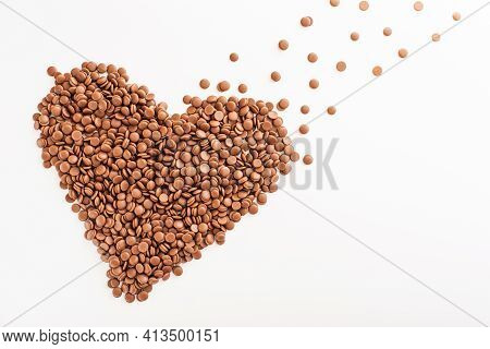 Chocolate Callets In Bulk On A White Background In The Form Of A Heart. The Concept Of Tempered Choc