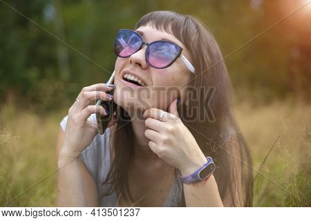 Young Woman Emotionally Speaks On The Phone On The Lawn On A Sunny Day. Happy Emotion On The Face.