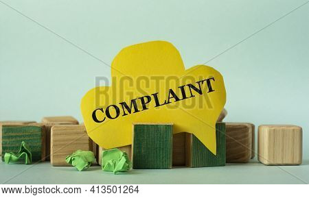 Complaint - Words On Yellow Paper Against A Background Of Scattered Wooden Cubes On A Mint Backgroun