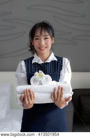 Young Hotel Maid With A Smile Holding Set Of Towel With White Flower. Staff In Blue Uniform Preparin