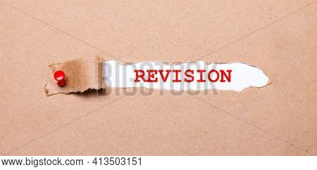 Beneath The Torn Strip Of Kraft Paper Attached With A Red Button Is A White Paper Labeled Revision