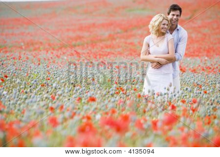 Couples In Poppy Field Embracing And Smiling