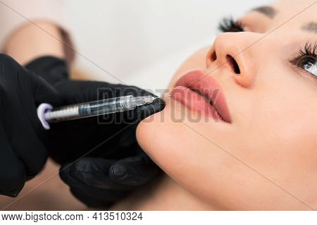 Hands Of Cosmetologist Making Injection In Lips. Young Woman Gets Beauty Facial Injections In Salon.