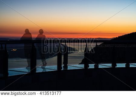 Tourists On The Glass Observation Deck At Sunset. Nature Park Biokovo. Croatia