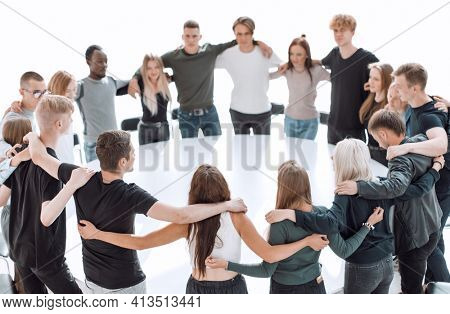 group of young like-minded people standing around a table