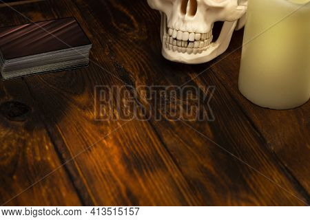 A Deck Of Cards For Fortune Telling On A Wooden Table. Oracle Attributes: Candle, Skull. Divination
