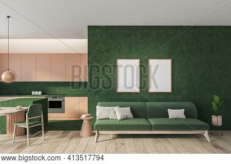 Two Blank Posters On Green Wall Above Green Sofa With Pillows On Parquet Floor. Kitchen Interior Set