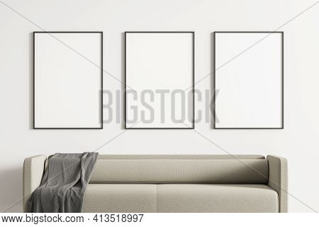 Close Up Modern Living Or Waiting Room Interior With Furnished By Beige Sofa And Three Blank Posters