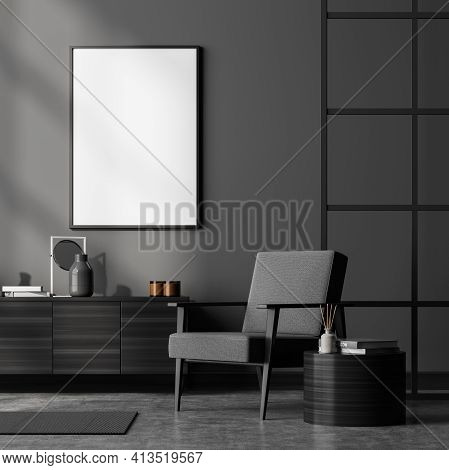Dark Living Room Interior With Grey Armchair, Wooden Drawer And Coffee Table With Books And Decorati