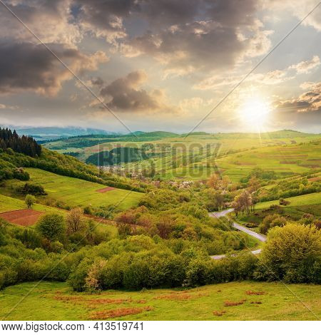 Carpathian Countryside In Spring At Sunset. Beautiful Rural Landscape In Mountain. Wet Grassy Meadow