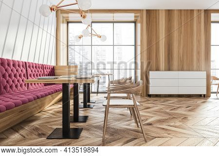 Modern Cafe Interior With Red Sofa And Table With Wooden Chairs In A Row. Windows With City View On