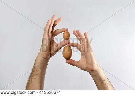Two Chicken Eggs Of Different Sizes Are Held In The Hands Of A Man.the Concept Of Size Comparison.gi