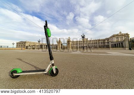 Electric Scooter On The Esplanade Of The Royal Palace Of Madrid In Sunny Day. Spain.