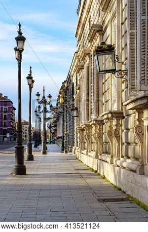 Sidewalk Of The Street Of The Royal Palace Of Madrid With Street Lamps And Old Building In Sunny Day