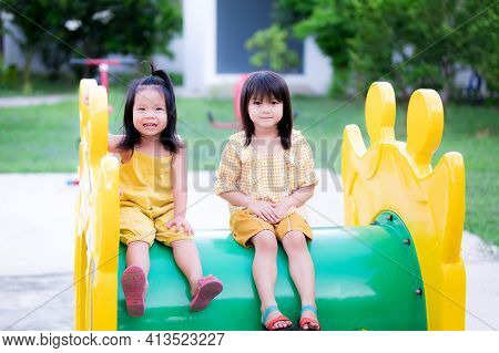 The Sisters And The Younger Sisters Sit On Children's Tunnel Player In Playground. Child Smiled Swee