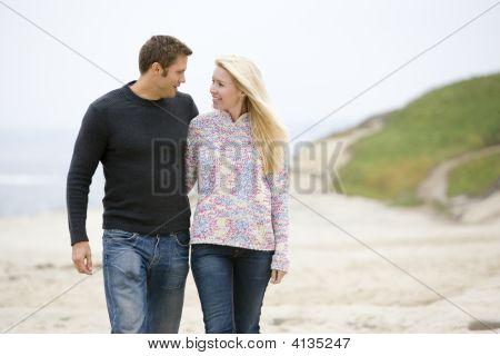 Paare, die zu Fuß am Strand lächelnd