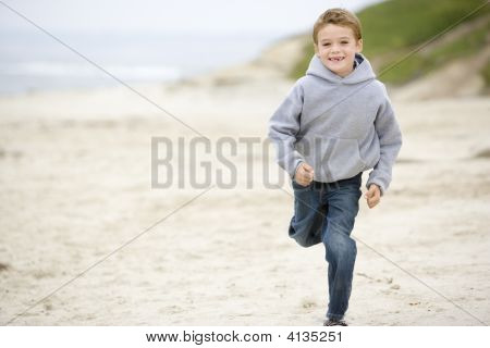 Young Boy Running On Beach Smiling