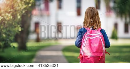 Girl With Rucksack Infront Of A School Building. Child With A Backpack