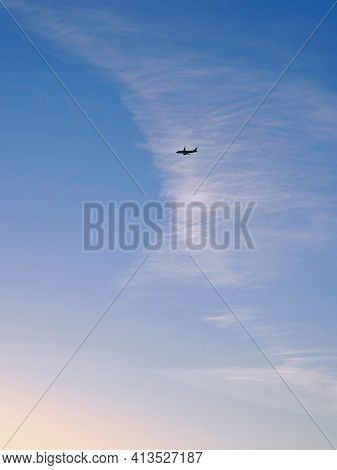 The Passenger Plane In The Distance Flies Towards The Sunset. Blue Sky And White Clouds. Vertical Il