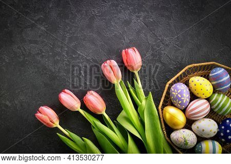 Basket With Easter Eggs And Pink Tulips On A Dark Concrete Background. Hello Spring And Easter Conce